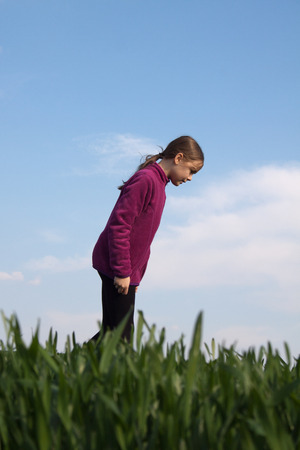 Young girl searches for something on the grass photo