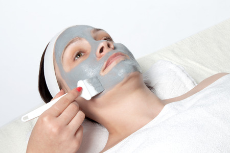 Beautician applied a young woman cosmetic facial mask with a brush photo