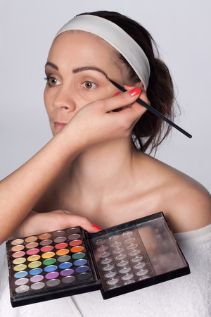 Beautician holding in one hand palette cosmetic shadows, and using a brush to apply color to the eyebrows of young brunette woman with headband on her head Stock Photo