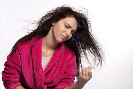 Young woman in bathrobe with messy hair and curlers