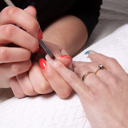 Manicurist applied with a brush on nails gel photo