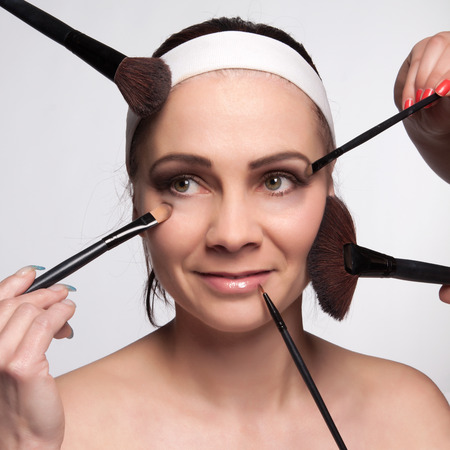 Close-up portrait young woman has around face brushes for different types of makeup photo