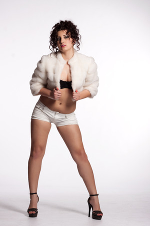 Young curly woman in white fur coat, shorts, black bra and high heels posing photo