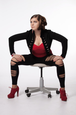 Young woman in red shirt, modern jacket, leggings with holes, red high heels, with exceptional haircut sitting on a swivel chair and posing photo