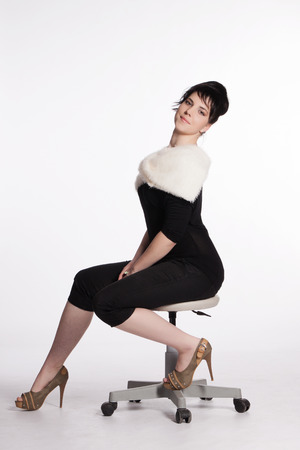 Portrait of a young woman in black with white fur collar sitting on a swivel chair photo