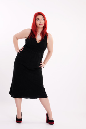 Young plump red-haired woman in black dress posing photo