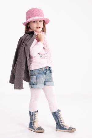 Little girl preschooler model in pink hat, coat, shorts and sneakers high with a scarf on her neck posing in studio photo