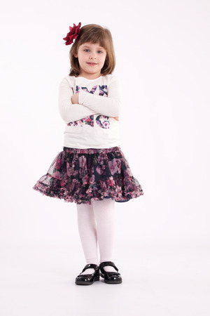 flowered: Little girl preschooler model in a flowered skirt with flower in hair posing standing in studio