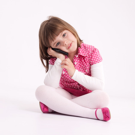 Little girl preschooler model in pink skirt, sandals and dotted shirt and sitting on the floor with mobile phone Stock Photo