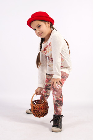 hand basket: The little girl in a red hat, holding a hand basket