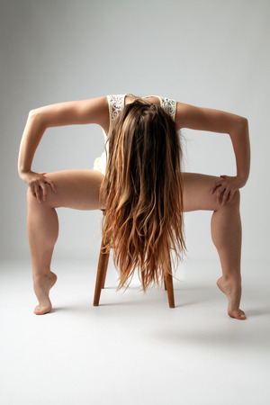 dissolved: Young long-haired woman sitting on a chair in ballet pose with dissolved long blond hair