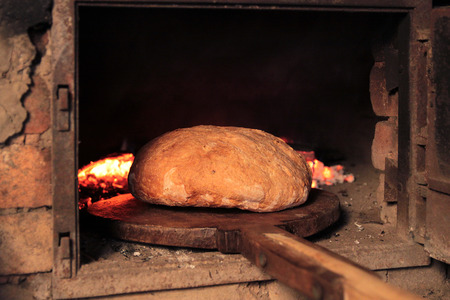 Bread baking in the old oven in the traditional way on carbon