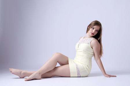 belles jambes: Jeune femme en robe jaune assis posant en studio