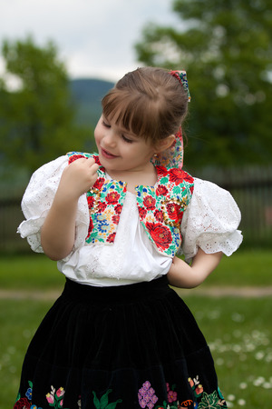 biased: Bambina in costume sul prato, tenendo farfalla Archivio Fotografico