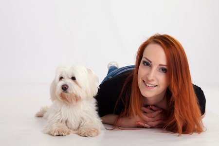 maltese dog: Young redhead woman with her white Maltese dog in studio