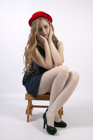 tights: Young long-haired curly blonde woman sitting sad