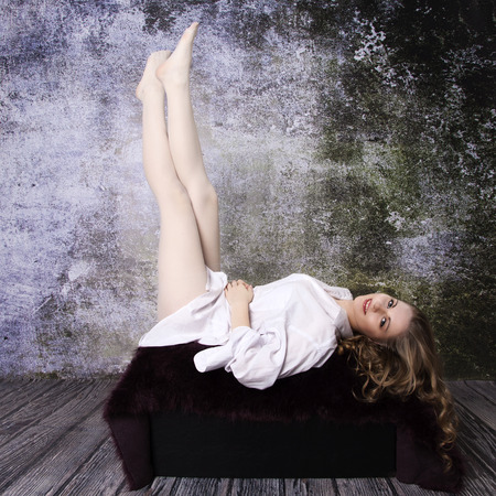 dilapidated wall: Young long-haired curly blonde woman on the sofa with a hairy blanket in front of an old dilapidated wall
