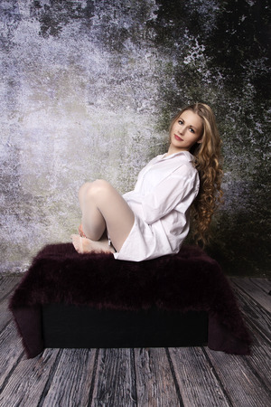 Young long-haired curly blonde woman on the sofa with a hairy blanket in front of an old dilapidated wall photo