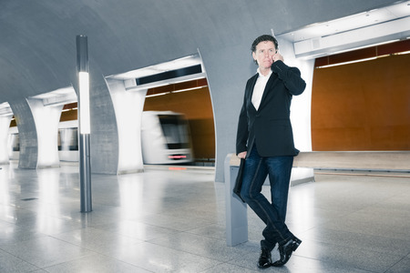 A young businessman with phone in the subway, blurred photo