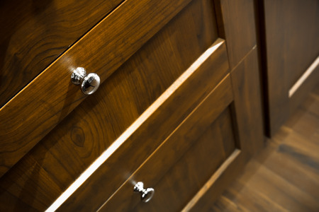 a wooden wardrobe drawer front, metal handle