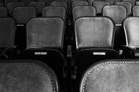 wood chairs in an old theater, black and white photo