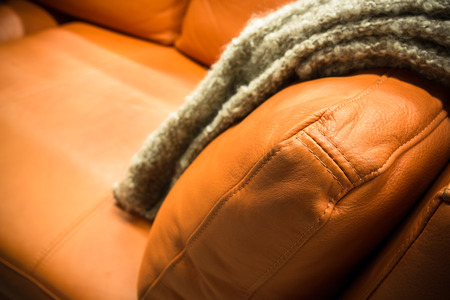 it is a gray blanket draped over a leather couch photo