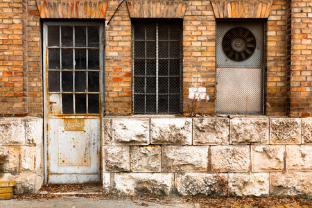 an old industrial building exterior wall, door and window photo