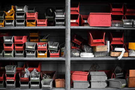gray, yellow and red plastic bins at sorting shelf in warehouse photo