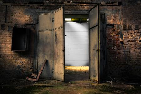 Oude roestige metalen deur in een verlaten pakhuis