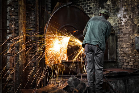 worker in factory cutting steel pipe using metal photo