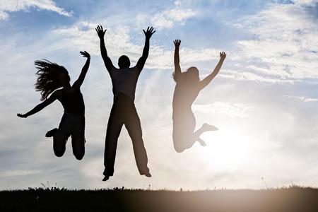silhouet groep van gelukkige jonge mensen springen in het park Stockfoto