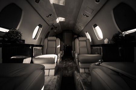 a luxury aircraft interior, leather seats, black and white Stock Photo