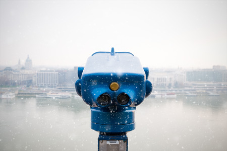 pay wall: community telescope in a lookout, view onto the city, snowfall Stock Photo