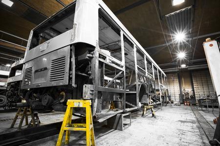 montacargas: una estructura de marco de autobuses durante la renovación de la tienda de reparación Editorial