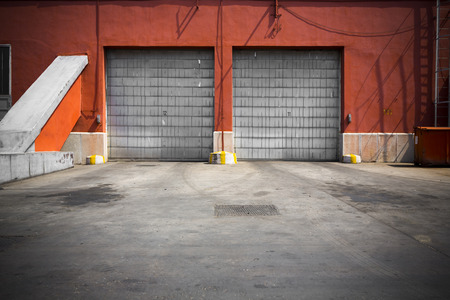 red door: an old industrial building metal garage door Stock Photo