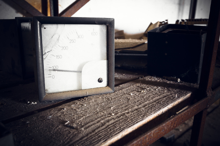 ampere: Old, dirty voltmeter in an abandoned factory, poor light