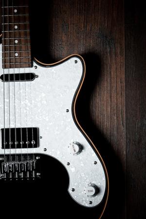 frets: an electric guitar details, close up, poor light