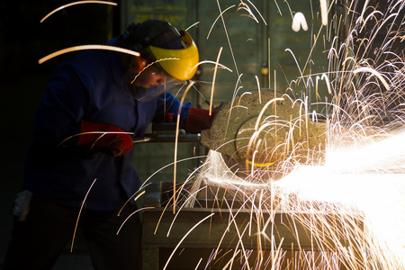 laborer: laborer working in a factory grinding machine Stock Photo