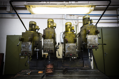 drilling machine: industrial drilling machine in a factory, poor light