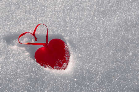 A red heart made of glass on white snow. Copy space. Foto de archivo