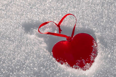 A red heart made of glass on white snow. Copy space.
