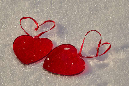 Two red hearts made of glass on white snow. Copy space.