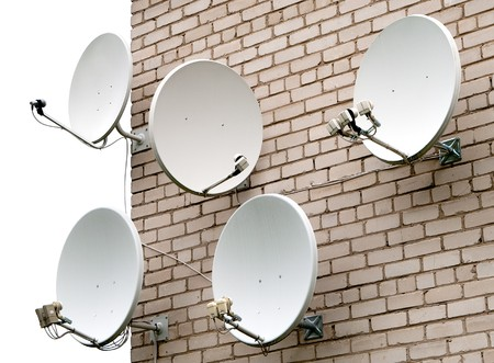 parabola: Five satellite antennas on the home front on the background wall of bricks Stock Photo