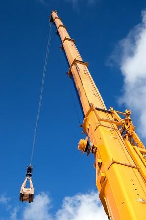 crane parts: Amarillo gr�a m�vil pluma hidr�ulica aumenta la carga contra un cielo azul
