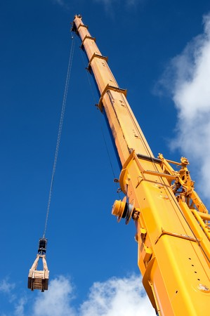 Yellow mobile crane hydraulic boom raises cargo against a blue sky Stock Photo - 4339983