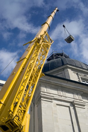 crane tower: Yellow mobile crane arm with hook against a blue sky Stock Photo