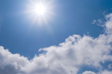 White clouds and sun on a blue sky photo