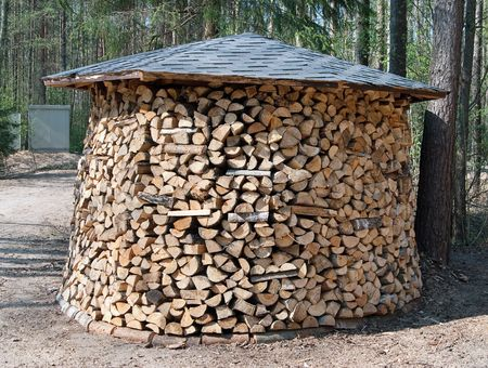 Chopped firewood stack. The huge woodpile combined in the form of a stack with roof photo