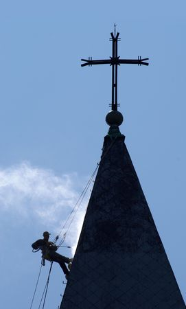 pressure washing: Climber silhouette on a dome of the church, carrying out works under pressure washing a roof