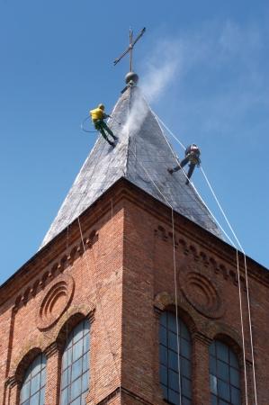 machine � laver: Deux alpinistes sur un d�me de l'�glise, la r�alisation de travaux sous la pression de lavage d'un toit